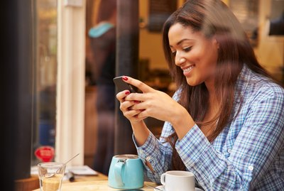 Woman Viewed Through Window Of Caf' Using Mobile Phone