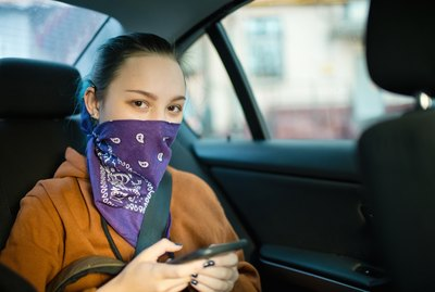 Teenage girl wearing alternative face covering bandana in a car with smartphone