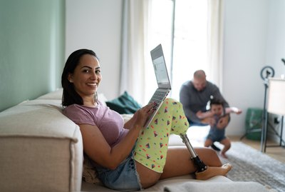 Portrait of a woman with disability working at home, family in the background