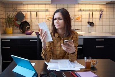 An attractive young housewife wears a shirt at home and examines gas and electricity bills. grimly considers spending this month and is under stress when checking accounts.