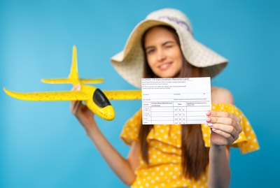 Selective focus. Covid 19 vaccine record card. Traveller girl holding an yellow airplane behind to coronavirus vaccination record card. New normal international tourism concept on blue background