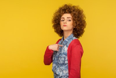 This is me! Portrait of proud confident egoistic woman with curly hair in casual outfit pointing herself