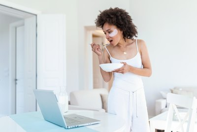 Beautiful young African American woman enjoys eating corn flakes for breakfast while working on her laptop in the morning. Looking at laptop computer and talking to her friends via video call.
