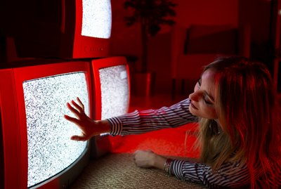 Young woman touching vintage TV screen while lying on front at home