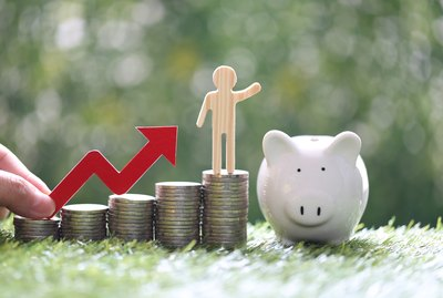 Business man on stack of coins money with hand holding red arrow graph and piggy bank on natural green background, investment and business concept