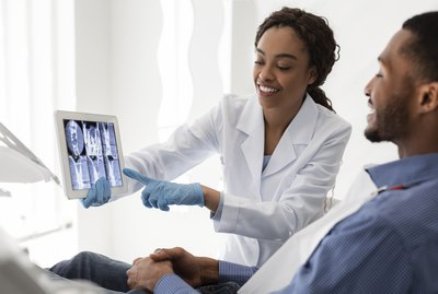 Smiling african female dentist showing patient teeth xray