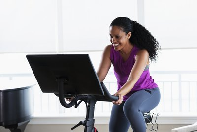 African-American woman on exercise bike at home