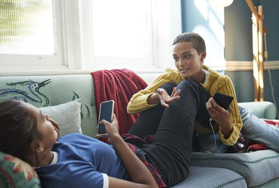 Friends talking while resting on sofa at home