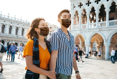 Asian couple traveling in Italy with protective face masks