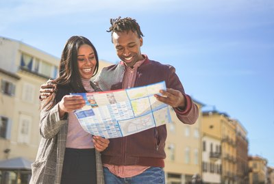 Black couple sightseeing the city centre during their holiday - Tourists checking on the map the main attraction of the city