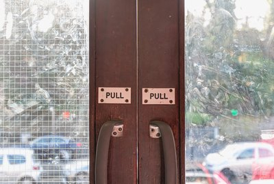 Pull engraved on plastic plate on wooden glass door of a metro station