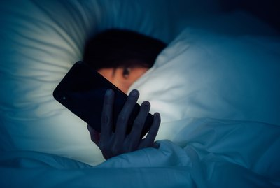 Woman hiding under the blanketed and using smart phone at late night on bed