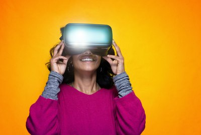 Beautiful young indian woman uses Vr glassess for augmented reality  - Pretty Sri Lanka girl uses technologic goggles posing with a yellow bright background