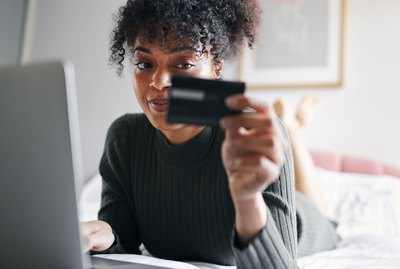 Young woman lying on bed at home with laptop computer using credit card to shop online