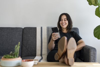 Woman sitting on couch with feet up on phone