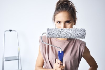 Young woman holding paint roller while standing at home