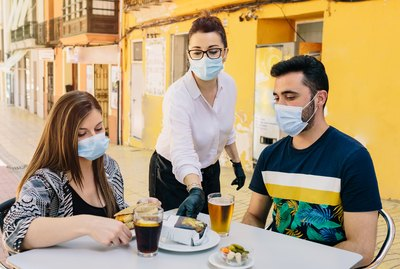 Clients with masks on the terrace of a bar in Spain attended by a waiter with gloves and masks. Social distancing