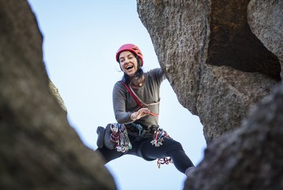 Low angle view of happy woman rock climbing