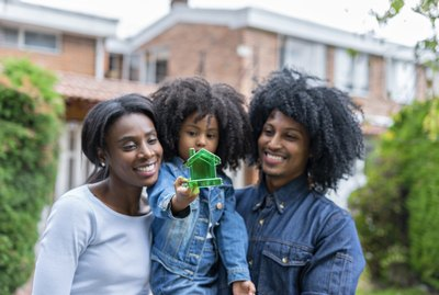 Afro-latin family, made up of mom and dad and a girl, pose smiling at the door of their new home.
