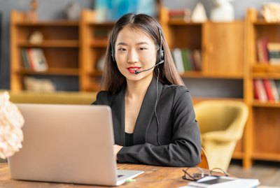Smiling chinese support service agent consulting customer. Female portrait looking at camera