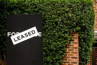 For lease and leased sign on a black display outside of a resedential building