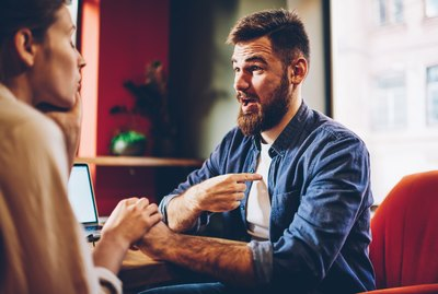 Wondered bearded young man solving conflict with girlfriend holding hands each other on romantic date.Surprised male discussing obligations with wife during quarrel sitting in restaurant interior