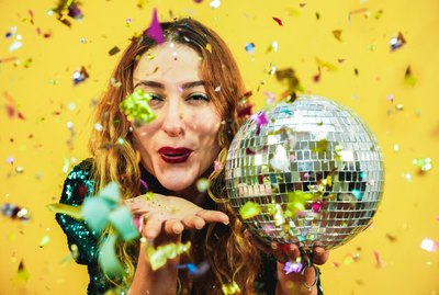 Happy fashion girl blowing confetti from hands holding a disco ball with yellow background - Young woman having fun at fest wearing trendy dress - Party, event and celebration concept - Focus on face