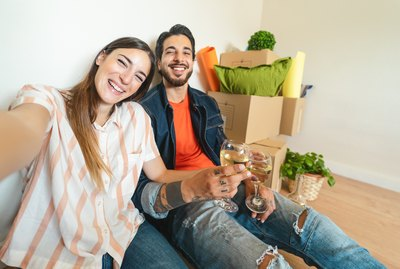 Happy young couple taking selfie while celebrating with champagne in new home first time - Change apartment day and people lifestyle relationship concept