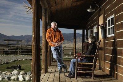 Senior man and woman having conversation on porch, smiling