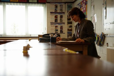 Mature female teacher marking papers at desk in classroom, side view