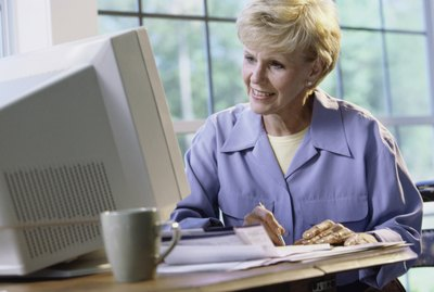 Senior woman sitting in front of a computer monitor