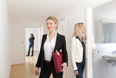 Young couple looking for real estate with female realtor