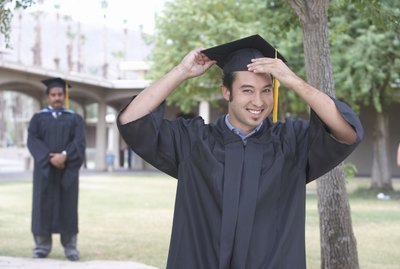 Young graduate student holding mortar board, portrait