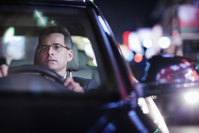 Businessman driving at night in the city