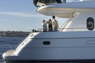 Senior couple and mature couple toasting each other with drinks on yacht
