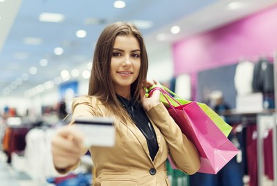 Beautiful woman showing credit card in shopping mall