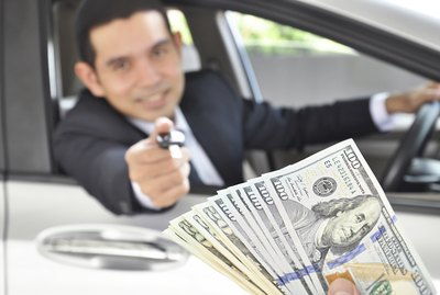 Man giving car key exchanging with money  - car pawn
