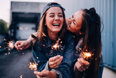 Girlfriends laughing and cuddling with sparklers