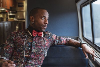 Fashionable young Black man looking out train window