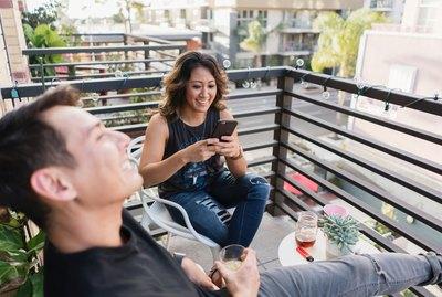 Two friends drinking wine on a balcony