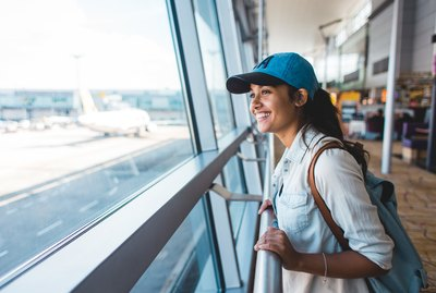 Excited young woman at airport gate window