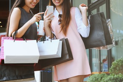 Two young women with lots of shopping bags plus phone