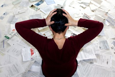 Woman overwhelmed by forms and receipts