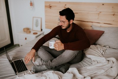 Young man with mug working on laptop on unmade bed