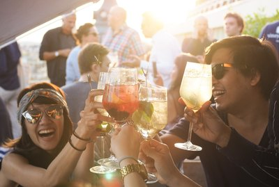Partygoers toasting in golden sunlight with cocktails