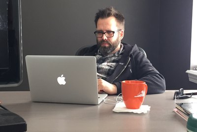Bearded tech guy working on Apple laptop