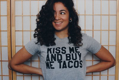 """Woman wearing t-shirt: """"Kiss me and buy me tacos"""""""