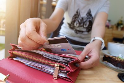 Woman removing credit card from wallet