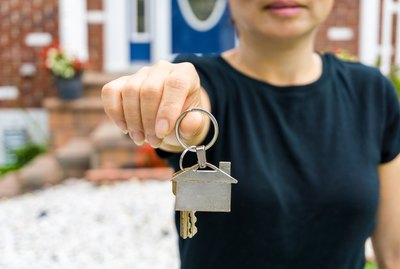 Woman holding keychain and keys with house on it