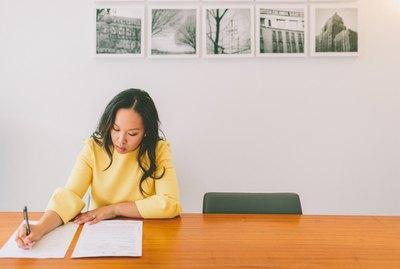 Woman in yellow sweater doing paperwork